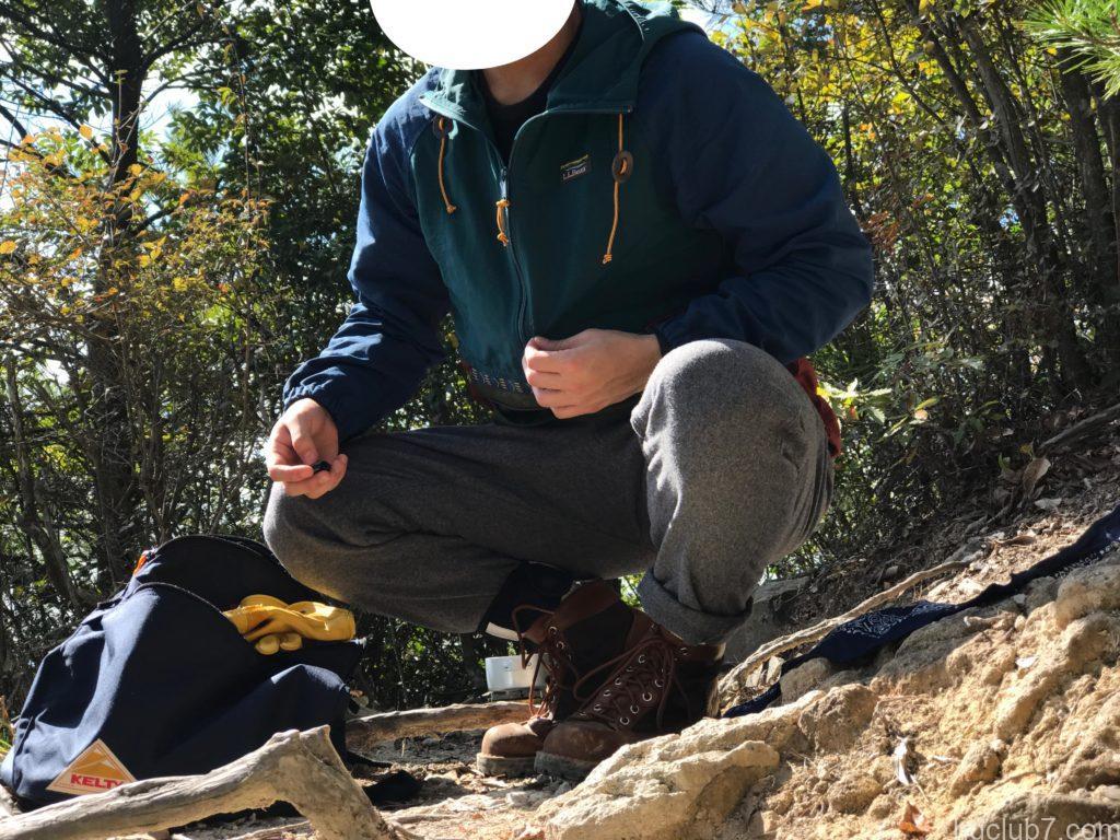 グラミチのウールブレンドタックテーパードパンツとエルエルビーンのアノラックパーカーを着て登山している男
