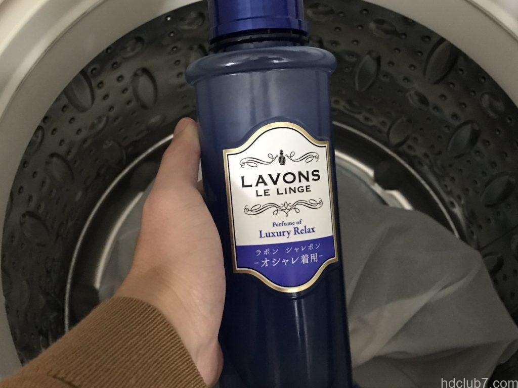 洗濯機に入れられたクロックスのクラシックスリッパと洗剤