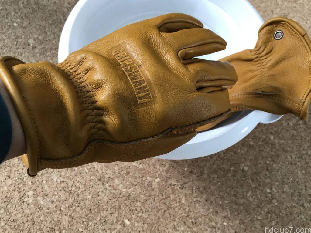 洗濯直後の濡れたグリップスワニーのレザーグローブを手にはめている