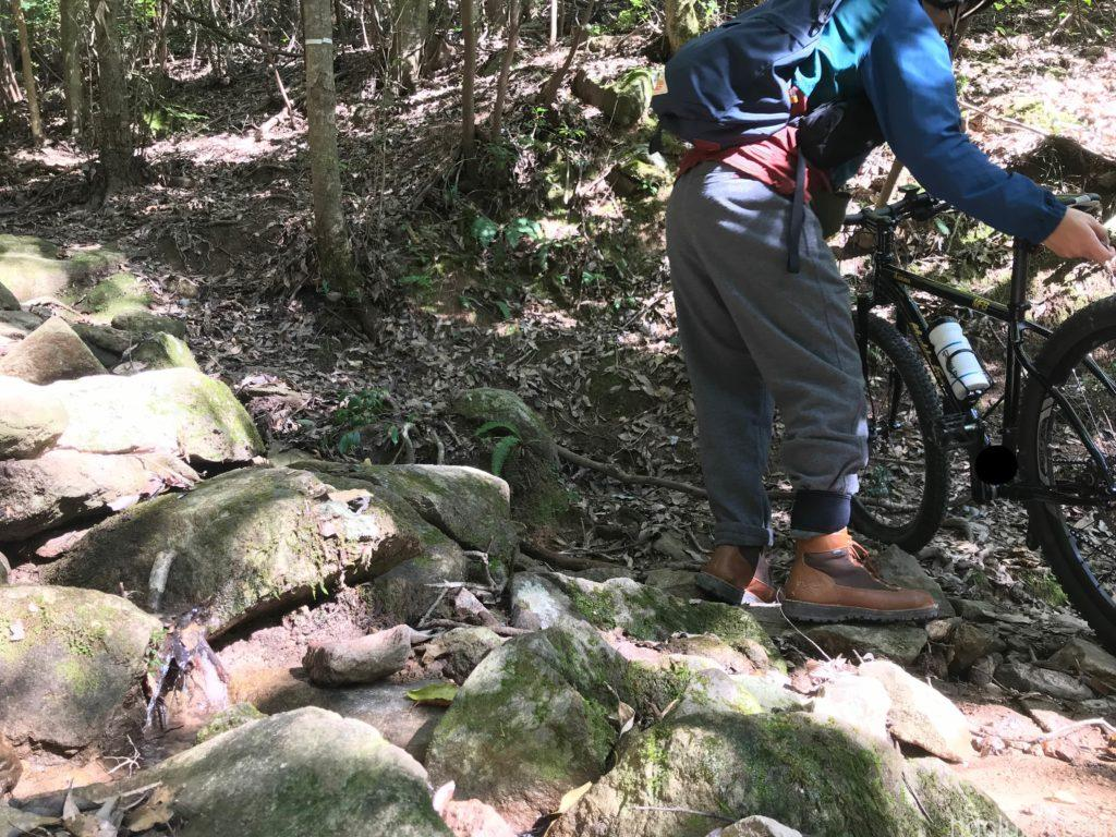 エルエルビーンのアノラックを着てマウンテンバイク担ぎ登山をしてる男