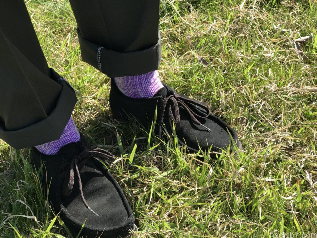 新品のディッキーズ874のオリーブグリーンとクラークスの黒ワラビーで野原に立つ人