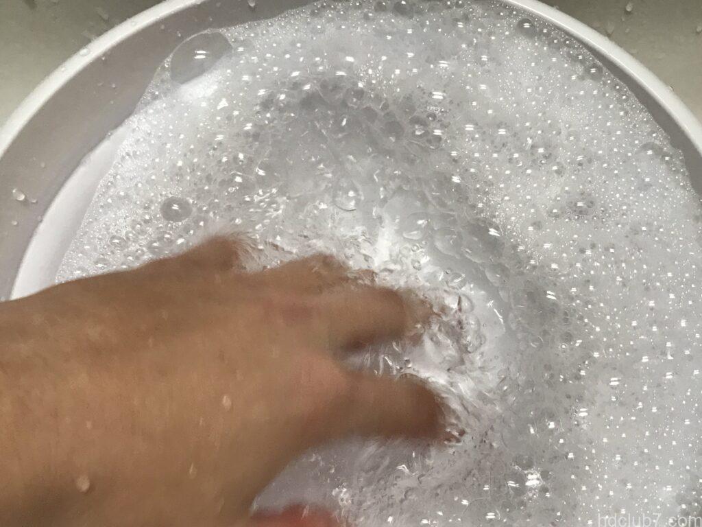 洗面器で洗剤を泡立てている