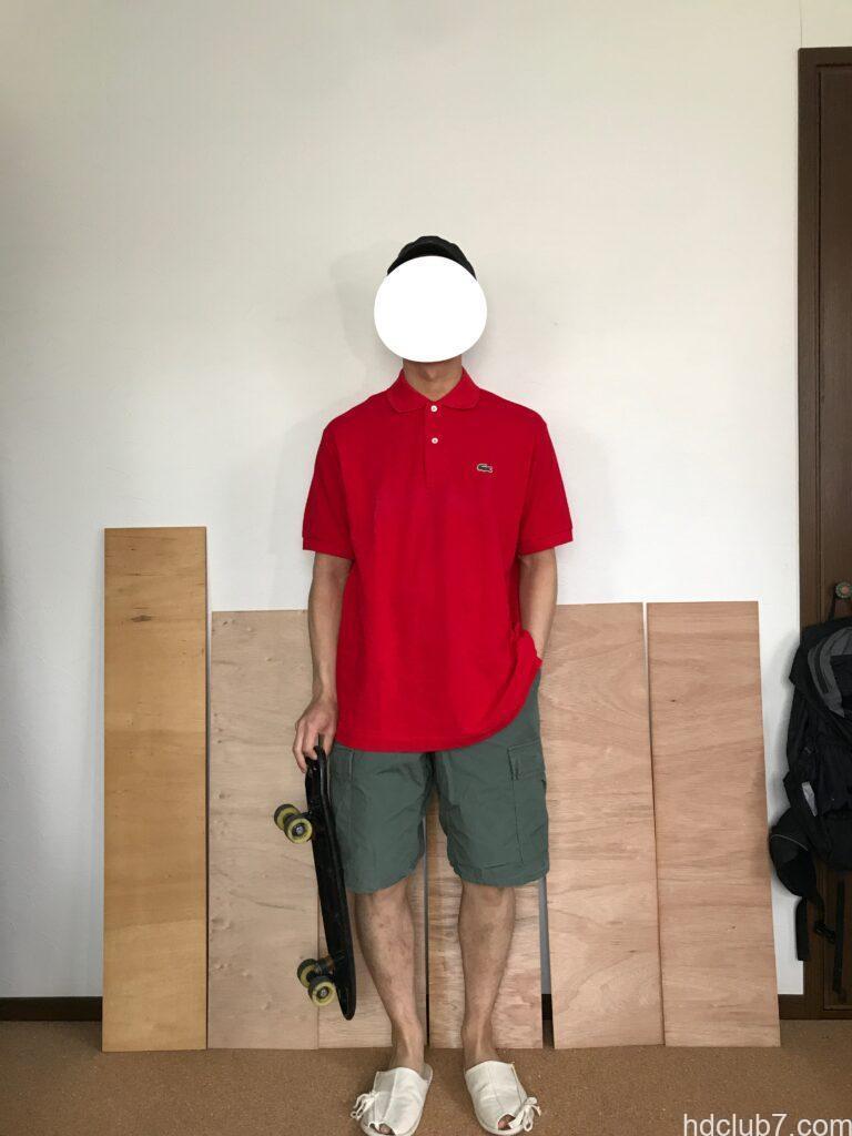 プロッパーのBDUカーゴショーツとラコステのオーバーサイズのポロシャツ着てスケボーを持ってる人