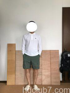 ロールアップしたプロッパーのBDUカーゴショーツとラコステの長袖ポロシャツを着て立っている男