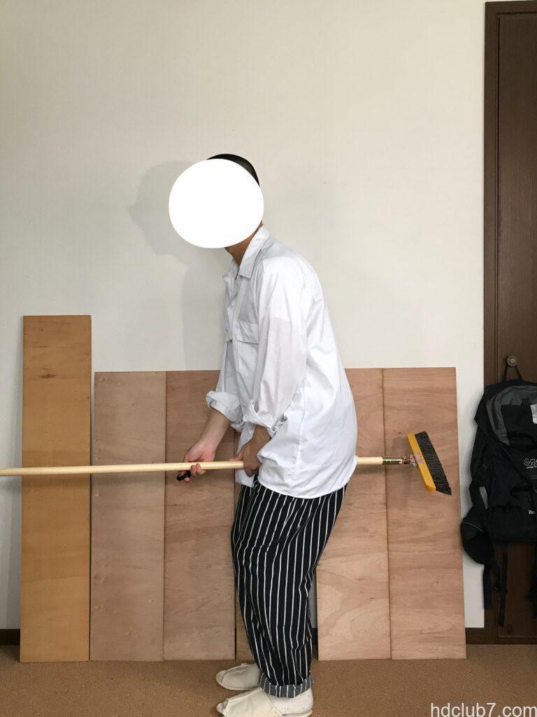 レッドキャップのシェフパンツとディッキーズの長袖ワークシャツ574を着て箒にまたがっている人