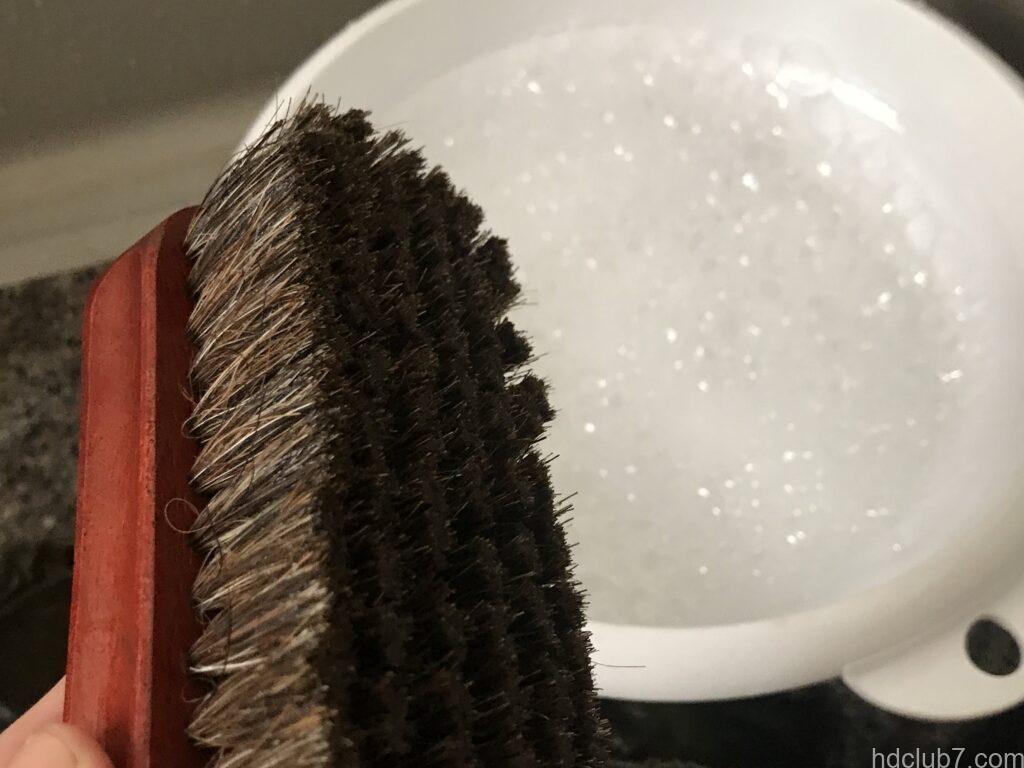コロニルの馬毛ブラシと洗面器に張られた洗濯液